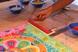 Colored sand is carefully poured onto the surface to create the intricate patterns of the mandala.